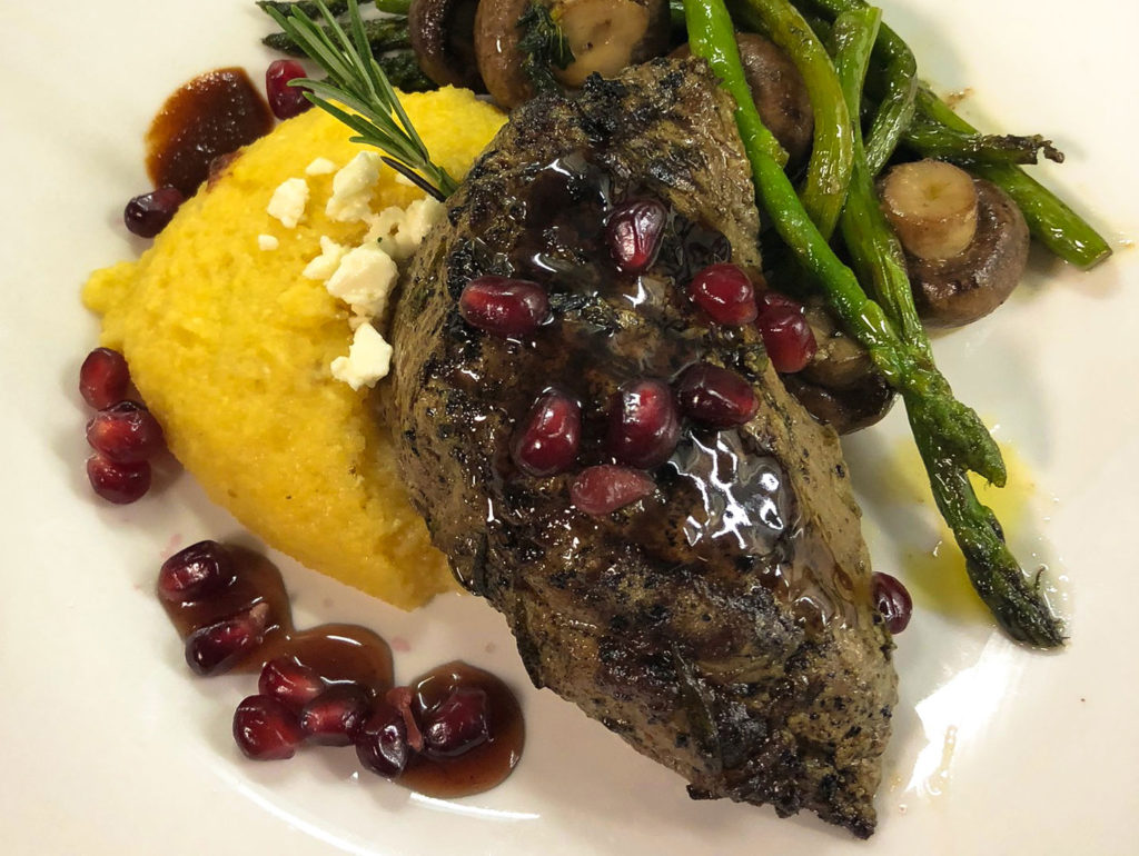 Chargrilled New York steak with a pomegranate port reduction, polenta with chef smoked goat cheese crumbles, Cabernet roasted Crimini mushrooms with sautéed asparagus, served with warm bread.